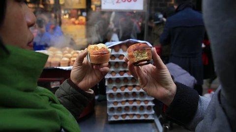 Asian woman eating street food, egg bread at Myengdong street in Seoul, South Korea