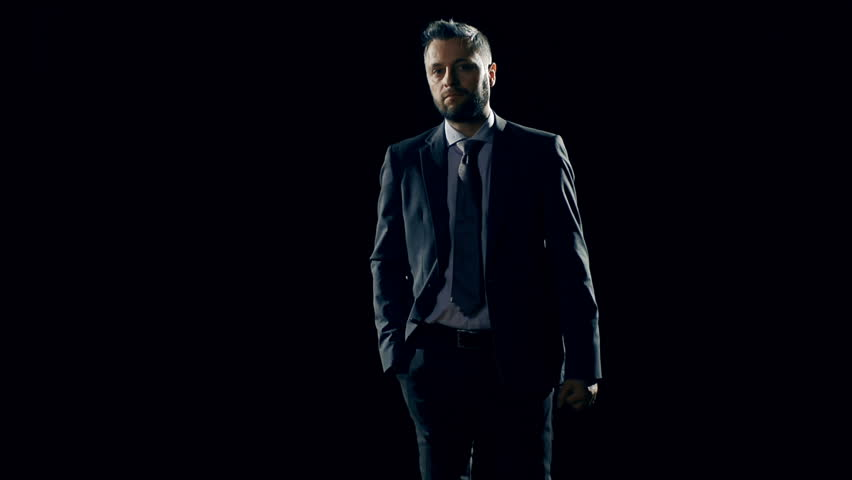 Businessman stepping out of the darkness and standing confidently against spotlight