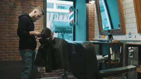 Barber shave the beard of the client with trimmer