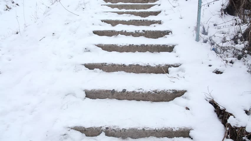 Man falling down the icy stairs. Man is walking up the icy stairs covered with snow. He slips and falls down.