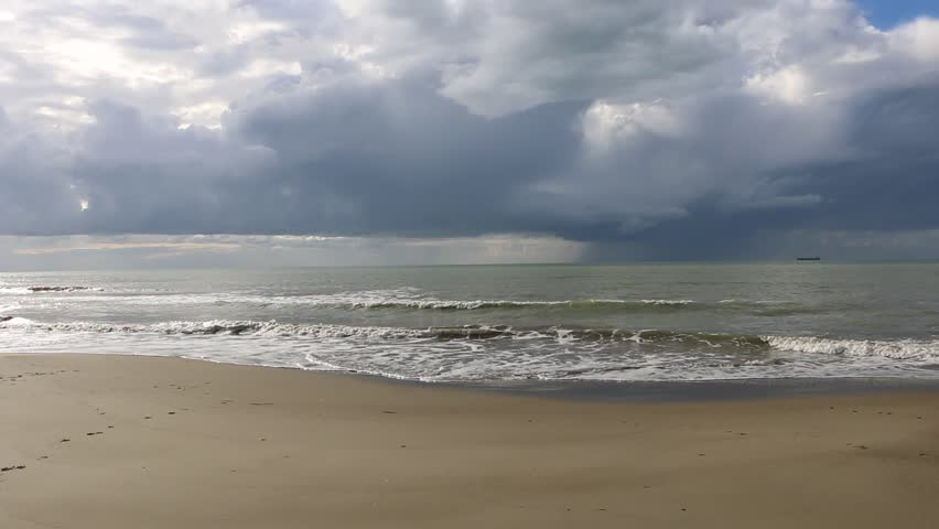 Stormy Adriatic Sea. Heavy dark clouds. Drops of rain falling down. Waves licking the shore.