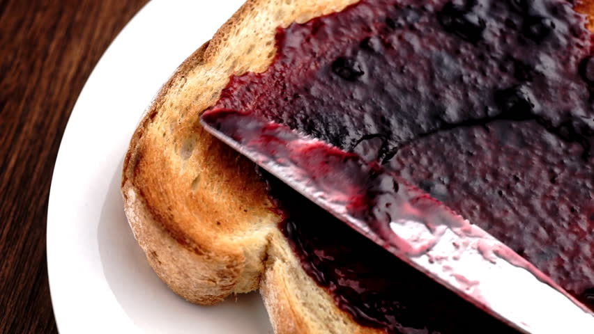 Spreading blueberry blackberry blackcurrant jam on crunchy toast in slow motion