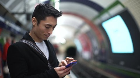 Young Asian man in a subway station using his phone as he waits for a train