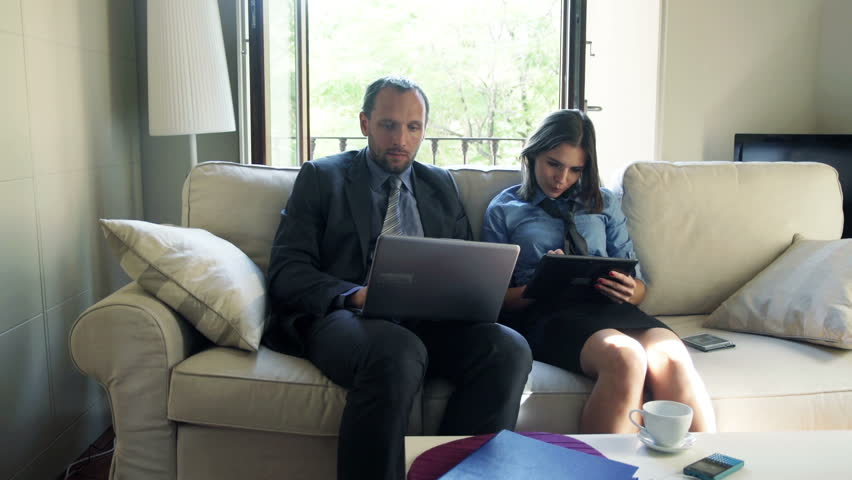 Business couple working on laptop and tablet computer sitting on sofa at home