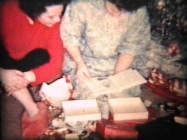 A family enjoys opening up Christmas presents together including the mother getting some new China.