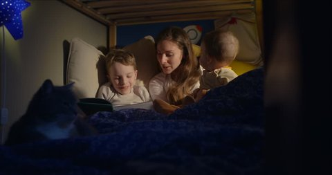 7 year old boy and his mum reading a bedtime story fix shot