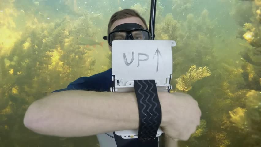 Diving sign- divemaster  writes on the plate and shows ok sign GO UP, ASCENT 2  of 4 also a available on the green screen all of diving signs from course