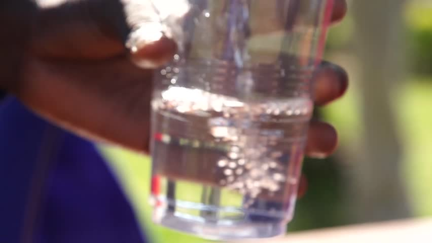 School children pour filtered water from their new water filtration system in Kakamega, Kenya.
