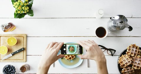 Top view man photographing breakfast using mobile phone Belgian waffles and coffee hands from above - Red Epic Dragon