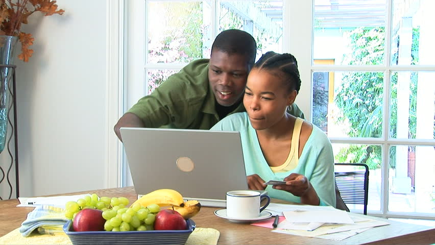 Young African American couple using credit card on laptop