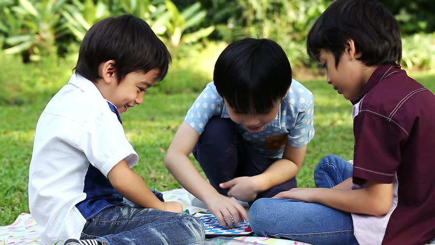 Three little boys playing a board game sitting in park