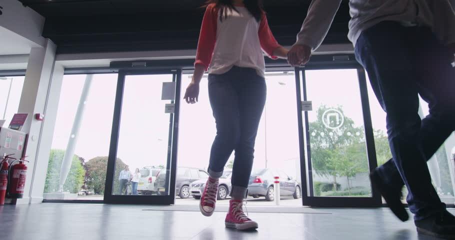 4K Couple entering large consumer electronics store showroom