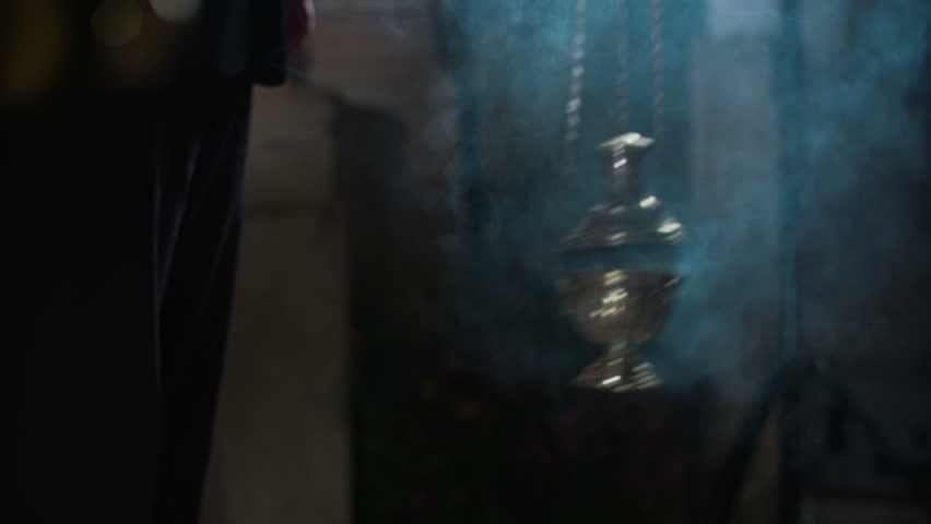Catholic ceremony with incense. Slow motion close up RAW footage of a Thurman swinging in the name of a Catholic ritual in the middle of the church.