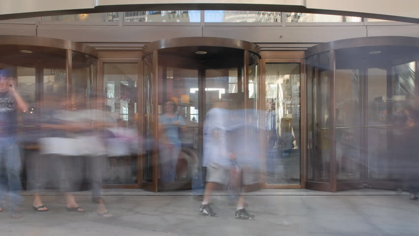 People spinning in and out revolving door time lapse