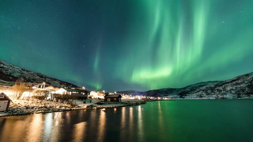 Northern Lights and city lights near Tromsø coast
