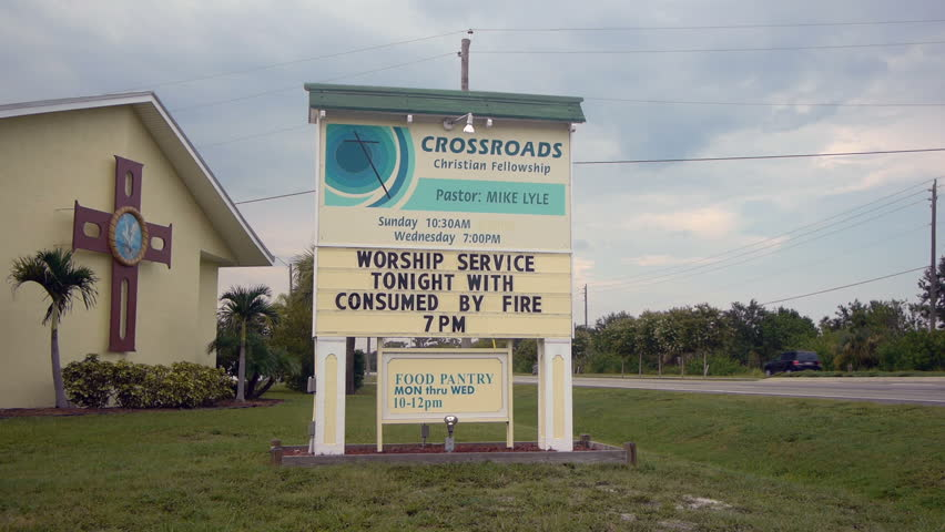 Vero Beach, Florida, USA. August 8, 2012. Crossroads church by the road in Florida with church sign reading 'Worship service tonight with... consumed by fire'.