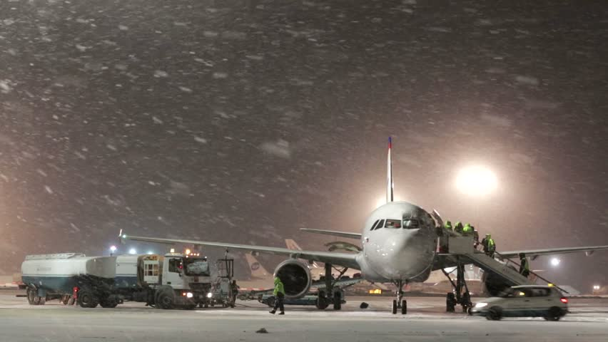 MOSCOW, RUSSIA - FEBRUARY 9, 2015: Snowstorm at the airport. Workers and service cars work near aircraft at the Domodedovo airport