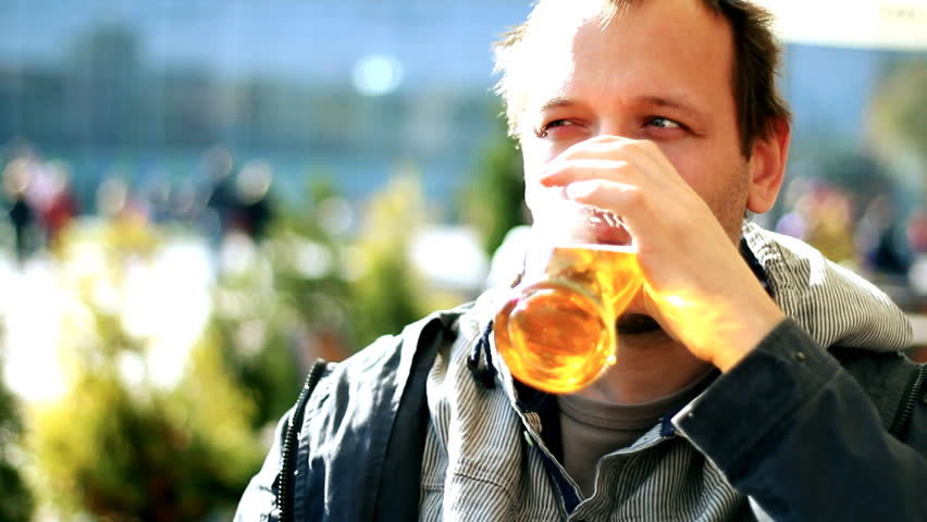 Man drinking beer outdoors,  steady cam shot