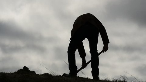 silhouette of man digging a hole with a shovel and wiping the sweat at the end slow motion 2