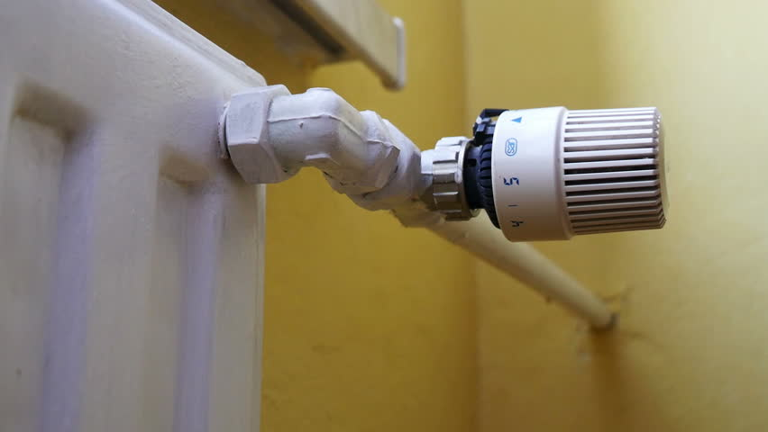A man regulates the thermostatic radiator valve to adjust heating at home.  / Thermostatic Radiator
