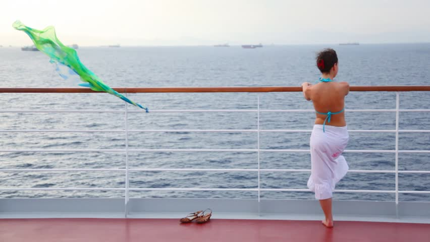 young woman stands on deck of cruise liner and looks at sea