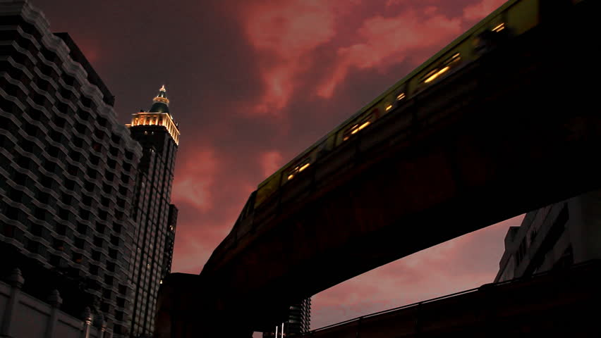Time lapse of Beautiful skyscraper, sky train passing and red clouds moving fast at sunset in downtown Bangkok, Thailand | Shutterstock HD Video #9112787
