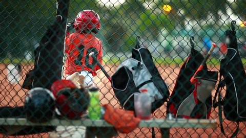 Shot from behind a fence at baseball field of baseball equipment such as bags and helmets and also of an unrecognizable kid swinging his bat during a game.