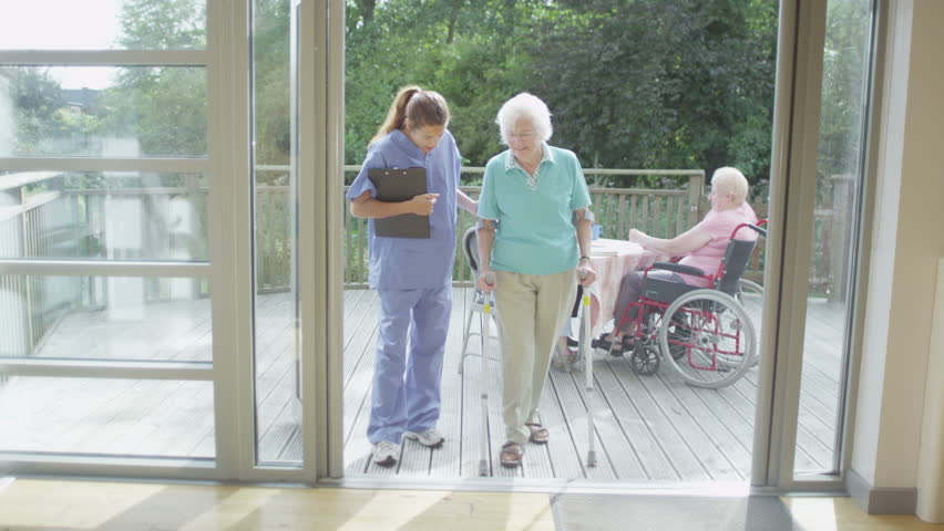 4K Caring nurse helping elderly female patient to walk in a hospital or residential care home