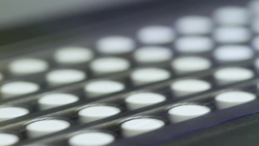 Pills at an automatic packaging line at a pharmaceutical factory are shot closeup