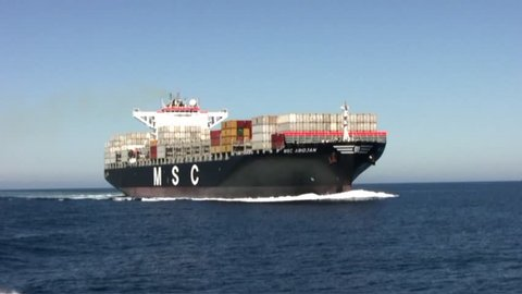 """VALENCIA, SPAIN – MARCH  07: The container ship """"MSC ABIDJAN"""" after leaving the port of Valencia is sailing in open waters, on march 07, 2015 in Valencia."""