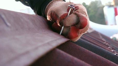 Builder hammering a nail, Mount installs a red roof with shingles. Close-up.