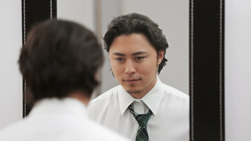 An attractive man wearing a shirt and tie, tying his tie in front of a mirror. Feeling confident and successful.