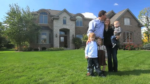 A happy family stands in front of their beautiful brick house
