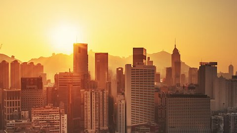 Sunrise cityscape skyline of Hong Kong. Warm yellow sun with scenic rays of light rising over modern city. Time lapse video