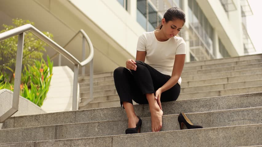 Portrait of latina woman walking in high heels and feeling pain, massaging feet with hand and sitting on stairs