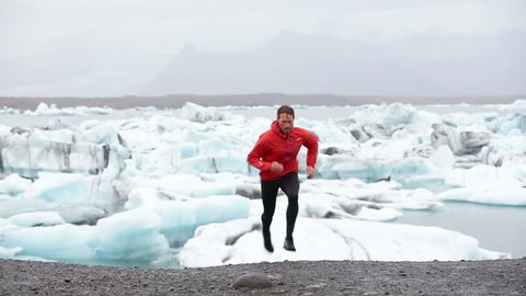 Running man. Trail runner training running uphill in beautiful nature landscape. Fit male athlete jogging and cross country running by icebergs in Jokulsarlon glacial lake in Iceland.