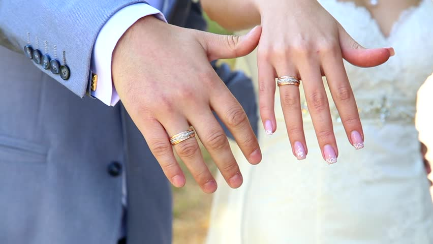 Bride And Groom Showing Gold Wedding Rings On Their Fingers Male Female Hands With