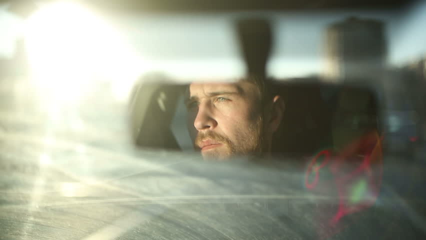 Man is driving a car. Reflection face in rearview mirror of vehicle. Time of sunset in a city #9303665