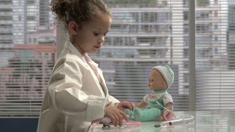 Little girl playing doctor with her doll
