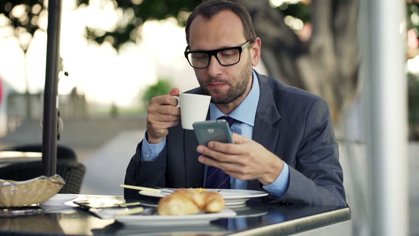 Young businessman using smartphone, drinking coffee in cafe in city  | Shutterstock HD Video #9316205