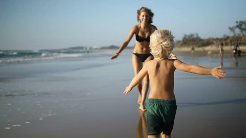 A little boy runs along the beach into her mothers arm's as the camera follows him. Slow motion