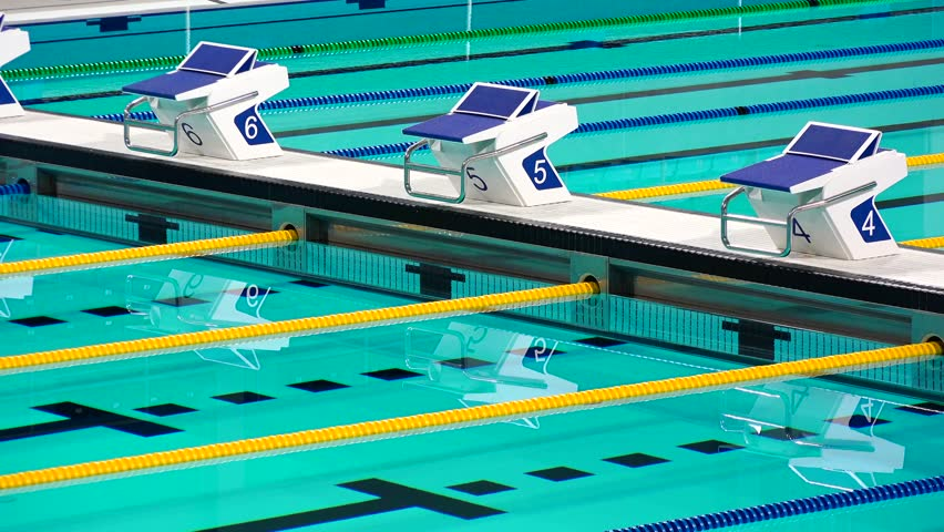 olympic indoor sport swimming pool start lanes with clear blue water moving in a soft breeze