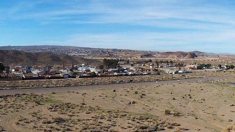 BARSTOW, CA/USA - March 5, 2015: Long shot from a distance of small town suburban homes in the desert. A small community neighborhood is nestled between hills and highway.