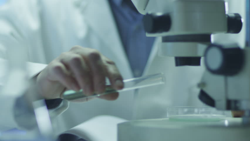 Scientist Does Research and Looks through Microscope. Shot on RED Cinema Camera in 4K (UHD). #9395837