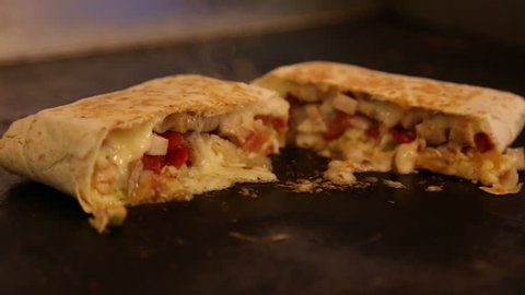 A professional chef is cooking Mexican food in restaurant, the tacos and quesadillas in cooktop, maize tortillas with cheese, tomato, lettuce, chicken and sauce-Dan