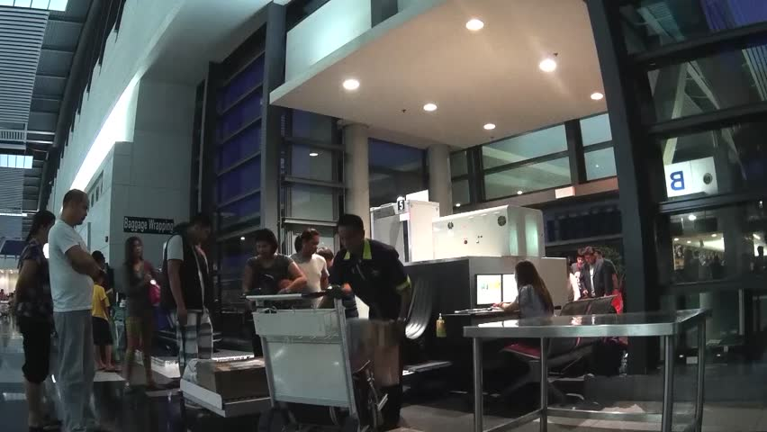 MANILA, PHILIPPINES - NOVEMBER 2, 2014: luggage are scanned by airport security at the Ninoy Aquino International Airport   Shutterstock HD Video #9407912
