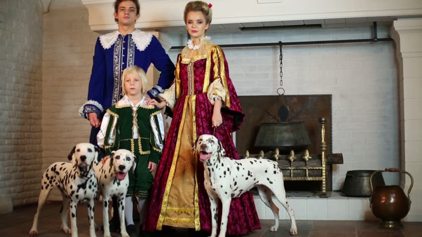 Father, mother and son in medieval costumes stand near fireplace with three dalmatians