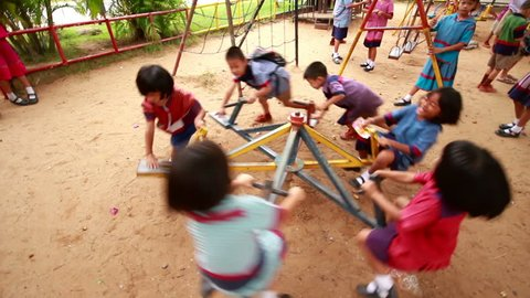 NAKHON RATCHASIMA, THAILAND - March 15: Kindergarten students in regional costume playing carousel in the playground. NAKHON RATCHASIMA, THAILAND - March 15, 2015