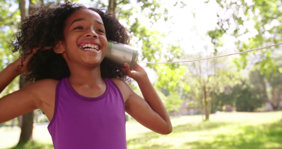 Happy young Afro girl smiling while listening to a tin can phone outdoors in a park in Slow Motion
