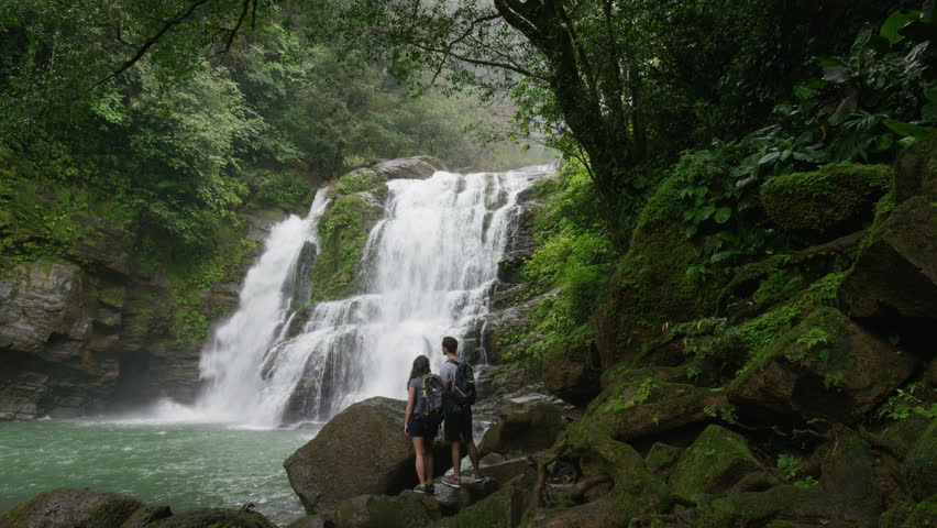 Wide slow motion zoom in of couple admiring waterfall in rain forest: Santa Juana, , Costa Rica